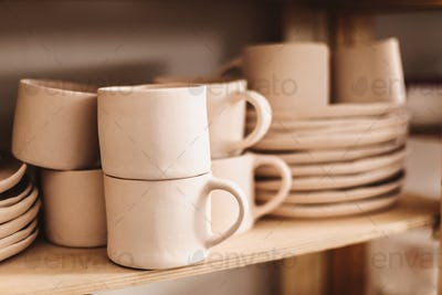 Close up handmade clay mugs and cups on wooden shelves at pottery studio