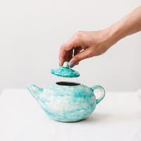 Close up photo of handmade colorful teapot at pottery studio isolated