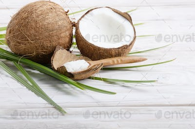 Coconut shell pieces and palm leaves on white wooden table
