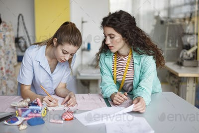 Young designers thoughtfully drawing sketches of new clothes wor