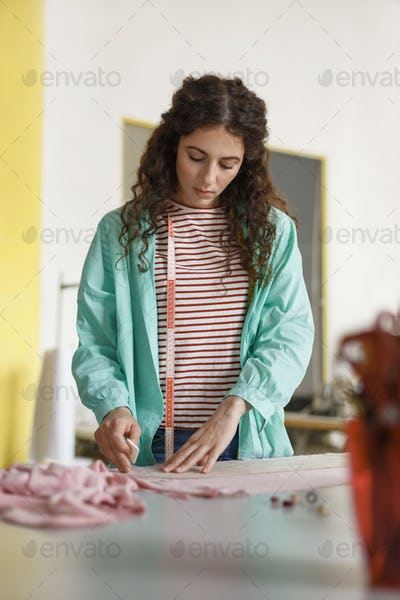 Beautiful designer of clothes in shirt and striped T-shirt dream