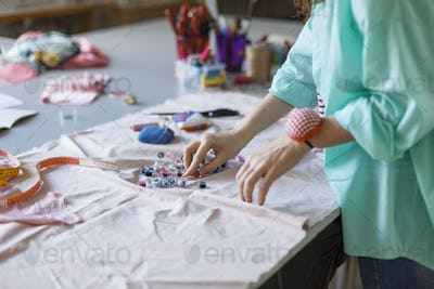 Close up tailor in shirt choosing colorful thread while working