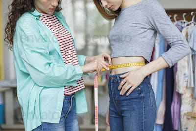 Close up young seamstress measuring girl waist with tape in sewi