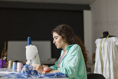 Young seamstress in colorful shirt thoughtfully working with sew