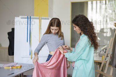 Young fashion designer dreamily choosing fabric with costumer in