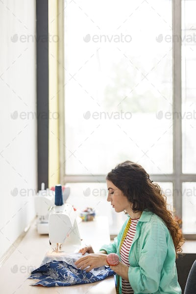 Young seamstress in colorful shirt thoughtfully using sewing mac