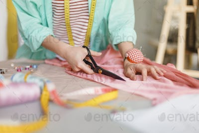 Close up seamstress cutting fabric with scissors in sewing works