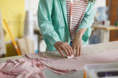 Close up designer of clothes drawing with soap on pink textile i