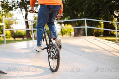 Close up young guy riding bicycle at modern skatepark isolated