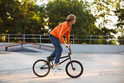 Cool young guy in orange pullover and jeans riding bicycle at sk
