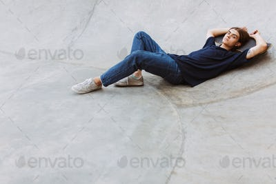 Young skater thoughtfully looking in camera while lying on skate
