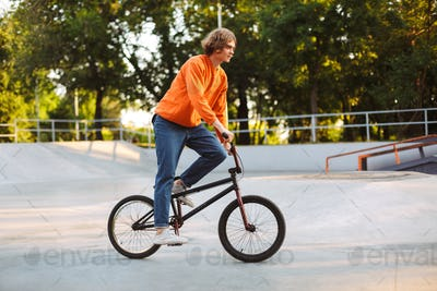 Young man in orange pullover and jeans riding bicycle at skatepa