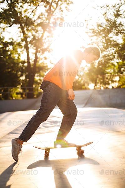 Young skater skateboarding while spending time in modern skatepa