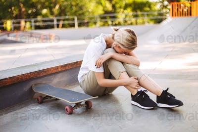 Young skater girl holding her painful leg and crying with skateb