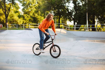 Young man in orange pullover and jeans dreamily riding bicycle a