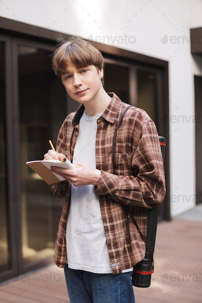 Portrait of young man standing with notebook and pencil in hands and dreamily looking in camera