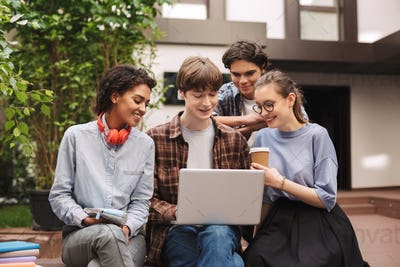 Group of young smiling students sitting on bench and working on laptop together