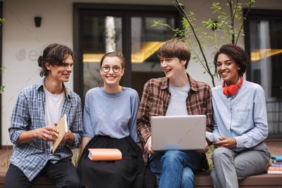 Group of smiling students sitting on bench with laptop and books