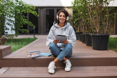 Pretty lady sitting in headphones with tablet in hands and happily looking in camera