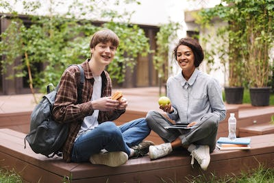 Couple of smiling students sitting on bench with sandwich and green apple