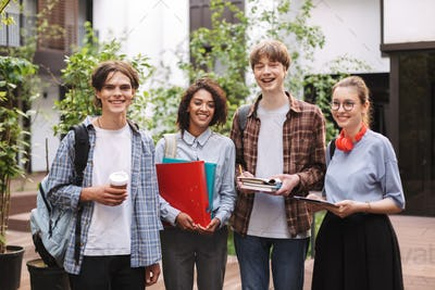 Young cheerful students standing with books and folders in hands and happily looking in camera
