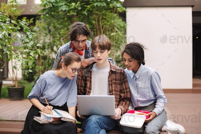 Group of young students sitting on bench with books and laptop on knees and studying together