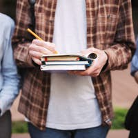Close up photo of young man holding pencil and books in hands
