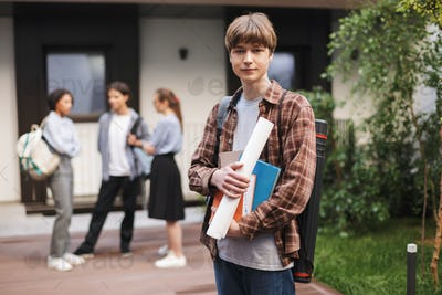 Portrait of young man standing with books in hands and dreamily looking in camera