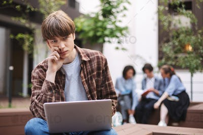 Photo of young tired man sitting on bench with laptop on knees and sadly looking in camera
