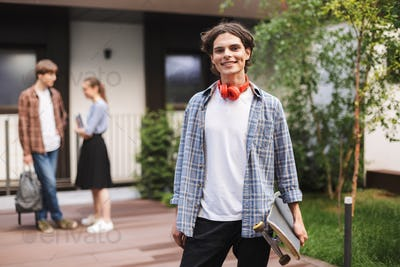 Joyful boy with red headphones standing and holding skateboard