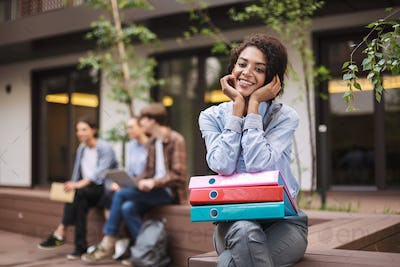 Smiling lady sitting on bench with colorful folders on knees and joyfully looking in camera