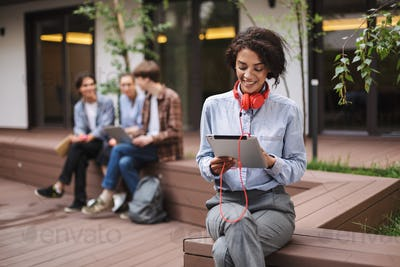 Smiling lady sitting on bench in courtyard of university with tablet in hands and red headphones