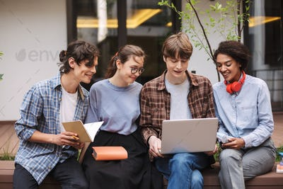 Group of smiling students sitting on bench with laptop and books in courtyard of university