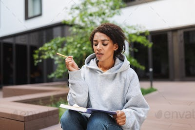Thoughtful lady with dark curly hair sitting with notebook on knees and studying alone