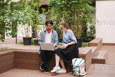 Couple of students sitting on bench with books and working on laptop in courtyard of university