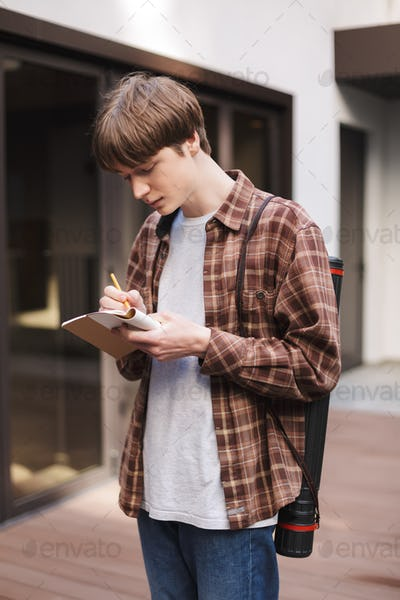 Portrait of young man standing with notebook and pencil in hands and dreamily writing notes