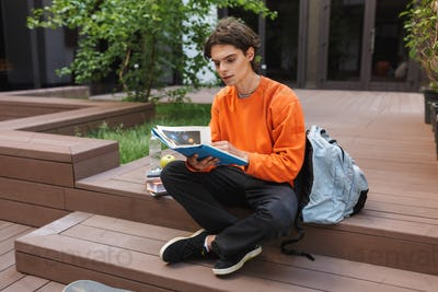 Young man sitting with big backpack and thoughtfully reading book in courtyard of university