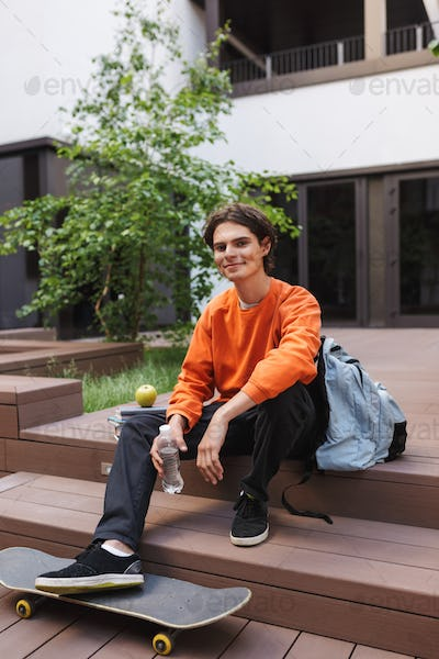 Young joyful man sitting with skateboard and happily looking in camera