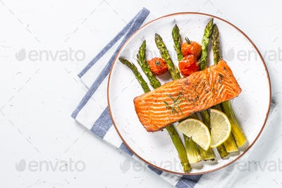 Grilled salmon fish fillet with asparagus on white