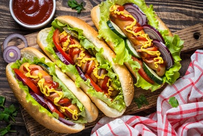 Hot dog with sausage and vegetables on wooden table