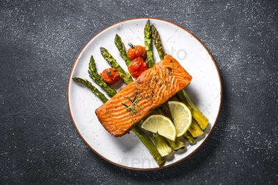 Baked salmon fish with asparagus top view