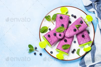 Blueberry ice cream popsicles top view on blue
