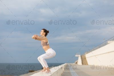 Young beautiful woman in sporty top and white leggings doing squ