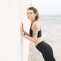 Young beautiful woman in dark gray sporty top and leggings dream