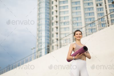 Young joyful woman in sporty top and white leggings holding purp