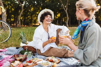 Pretty laughing girl sitting on picnic blanket with juice in han