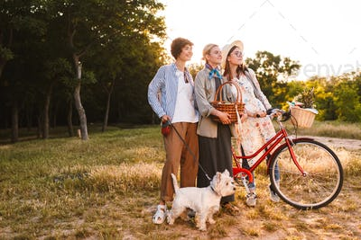 Beautiful girls with bicycle and wood basket in hands dreamily l