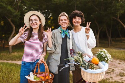 Group of beautiful smiling girls with bicycle and baskets full o