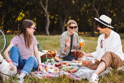 Group of beautiful girls sitting on picnic blanket happily spend