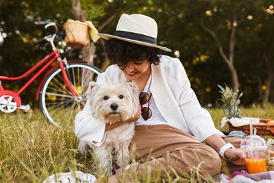Beautiful smiling girl in hat hugging little cute dog happily sp